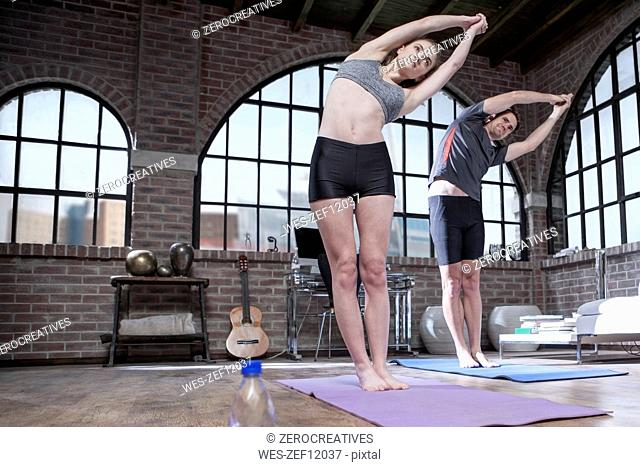 Young man and woman stretching in yoga studio