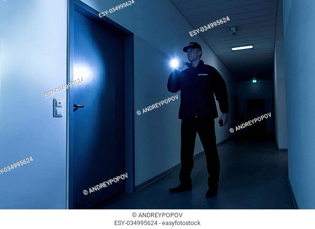 Full length of mature security guard with flashlight standing in front of door in building