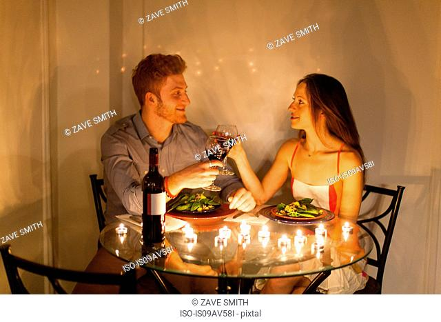 Couple at table face to face enjoying candlelit meal, making a toast, smiling