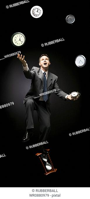 Businessman standing on hourglass and juggling with clocks