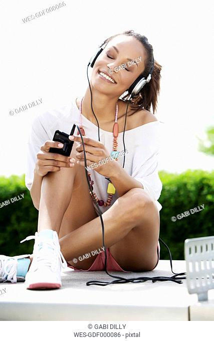 Germany, Young woman listening music with head phones, smiling
