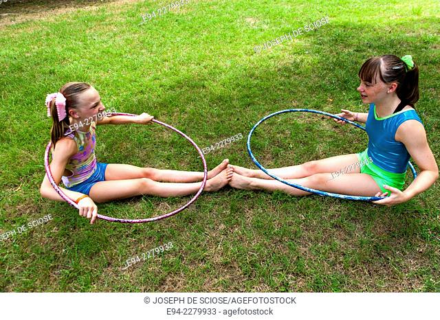 2 young sisters sitting on the grass holding hula hoops looking at each other