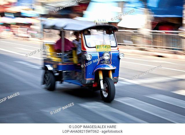 A Tuk Tuk passing along a road in Bangkok