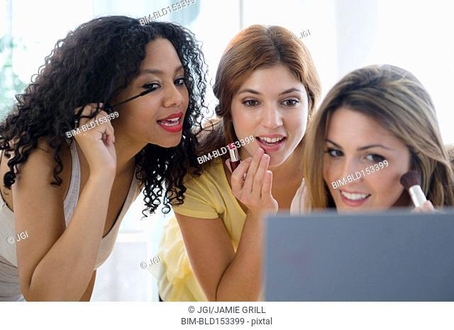 Women applying makeup in mirror