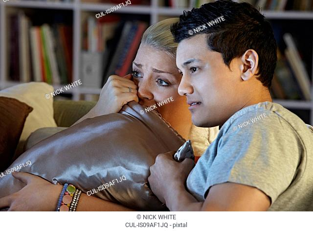 Young couple watching horror movie, hiding behind cushion