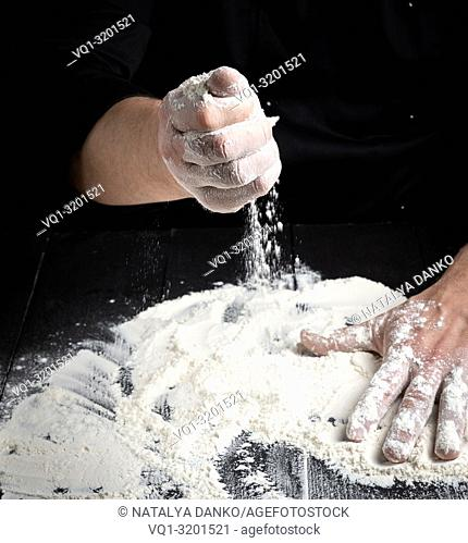white wheat flour on a black wooden table and the cook prepare to knead the dough