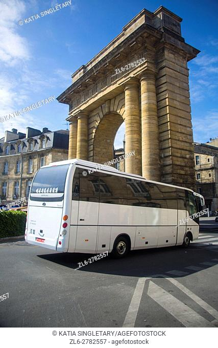 A tourist white bus passing next to one of the Arch entrance of the Old Town, It is spread out on a curve along the western side of the River Garonne