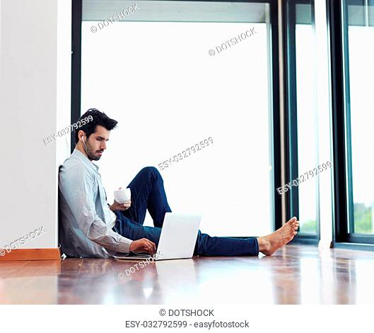handsome business man in casual clothing working on laptop computer from home and drink firs morning coffee