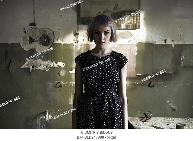 Serious Caucasian woman standing near dilapidated wall