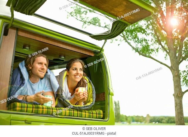Couple drinking coffee in trailer
