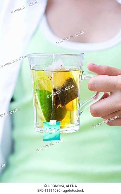 A girl holding a glass of tea with a wedge of lime