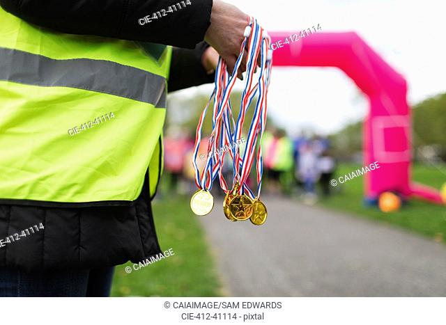Volunteer holding medals at charity run