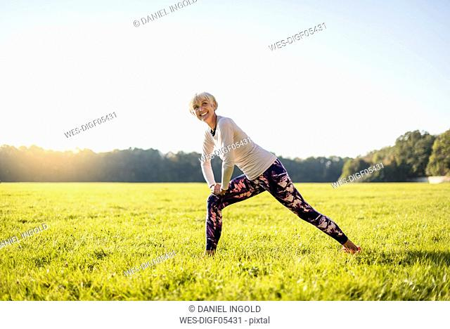 Smiling senior woman stretching on rural meadow