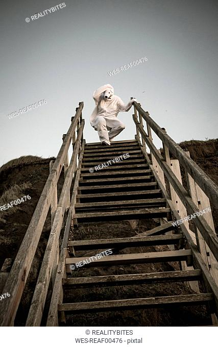 Man wearing ice bear costume on steps, despair