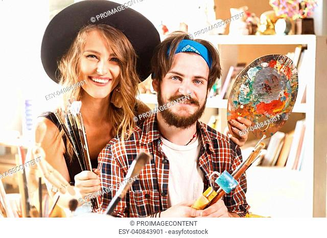 Portrait of cheerful happy female long hair artist in cute balck hat and bearded male artist in blue bandana holding brush and palette