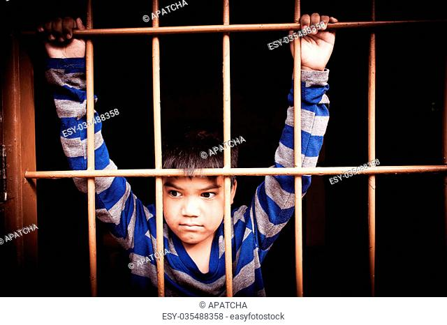 vintage of asian boy Hand in jail looking out the window