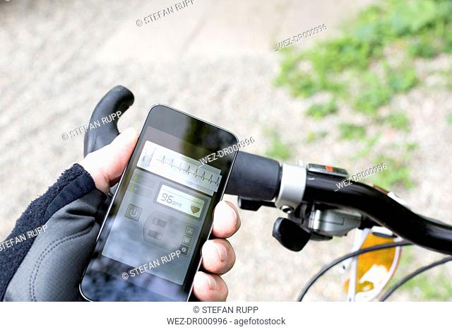 Hand of mountain biker holding smartphone with heart rate monitor