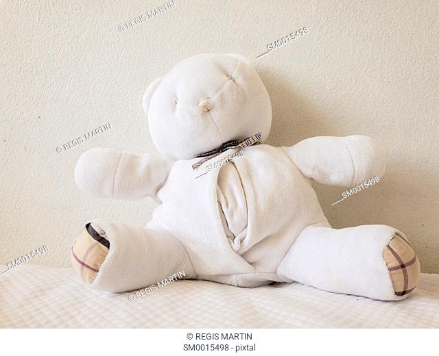 White teddy bear on a white bedcover against a white wall