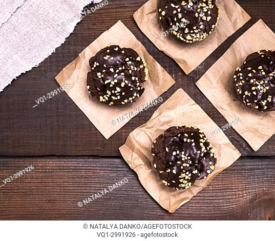 chocolate muffins are sprinkled with ground nut on pieces of brown paper, top view, empty space on the left