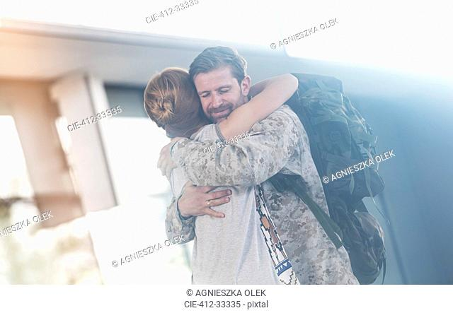 Wife greeting and hugging soldier husband at airport