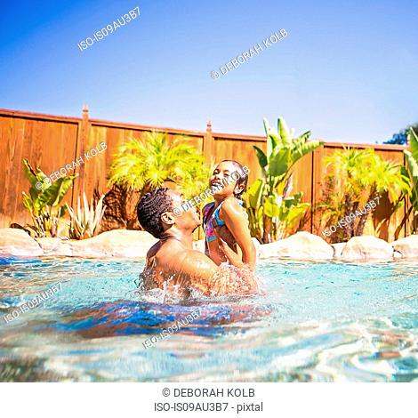 Side view of father lifting up smiling daughter in swimming pool