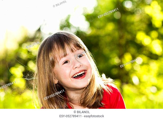 Portrait of happy smiling little girl on sunny summer grass meadow