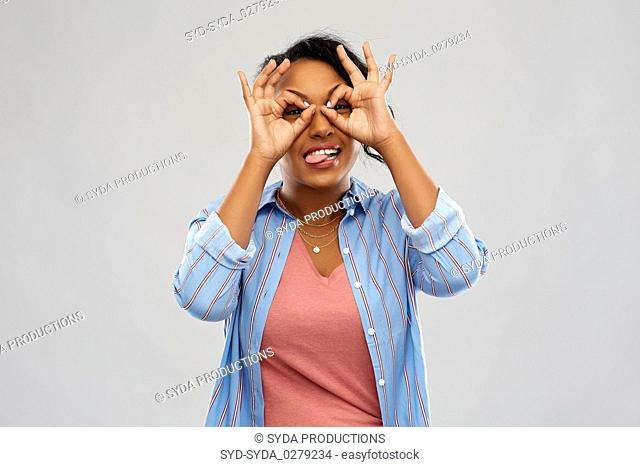 african woman looking through finger glasses