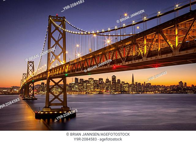 Twilight over the Oakland Bay Bridge with skyline of San Francisco beyond, California USA