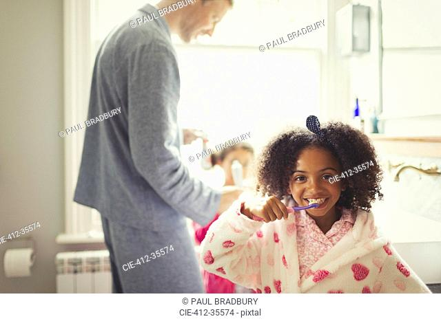 Girl in bathrobe brushing teeth in bathroom