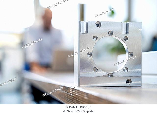Metal workpiece in factory with businessman in background