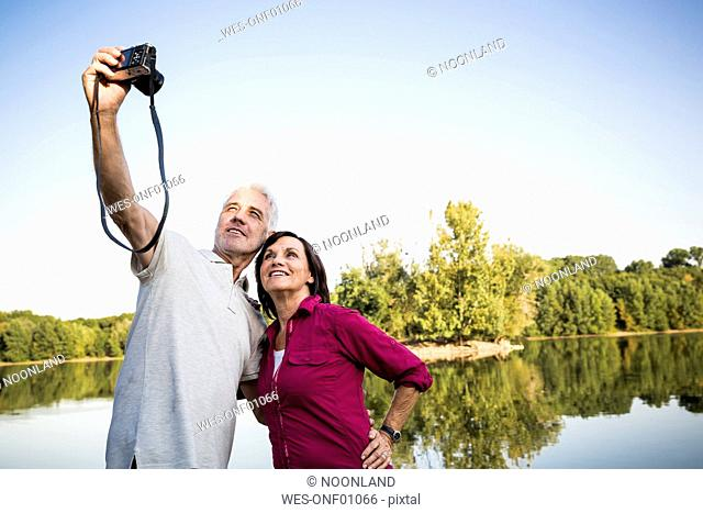Senior couple at a lake taking a selfie