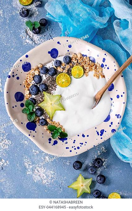 Smoothie bowl healthy breakfast. Yogurt with blueberries, granola, chia seeds, lime, wooden spoon, mint and carambola on textile gauze over blue concrete...