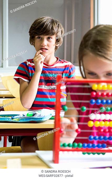 Portrait of pensive pupil at classroom