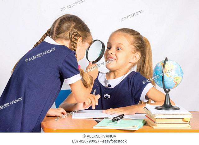 Girl looking at the other girl with a magnifying glass on a geography lesson