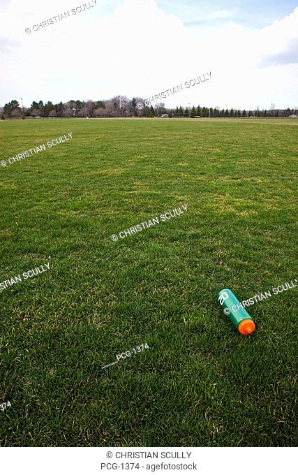 A sports ground, grass field, with trees on the horizon. A water bottle on the ground