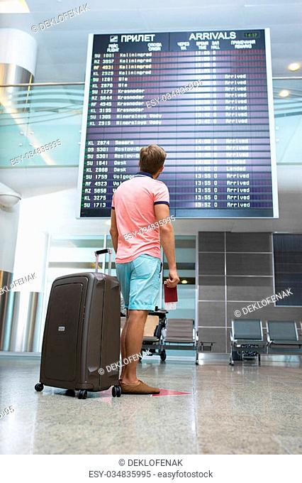 Young man with a suitcase at the board