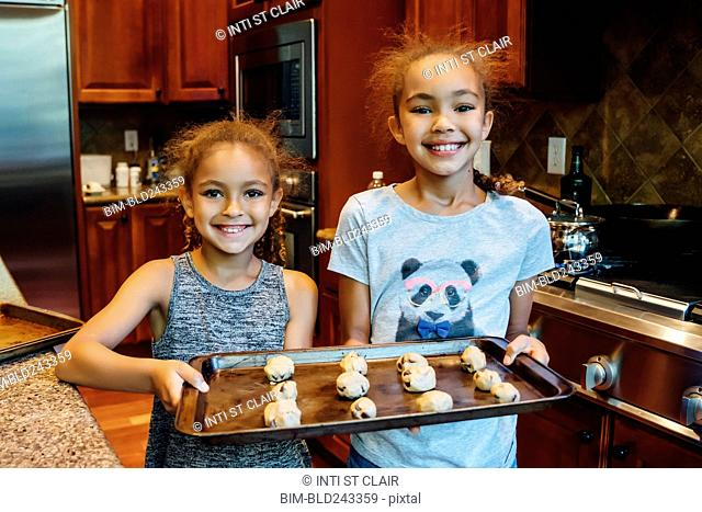 Mixed Race girls holding tray with cookie dough in domestic kitchen