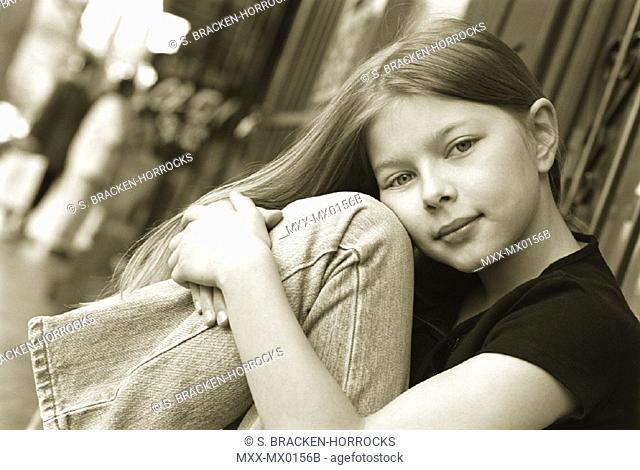 Young girl sitting outside on sidewalk