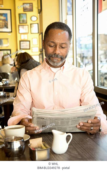 Mixed Race man reading newspaper in coffee shop
