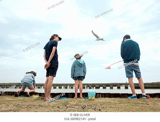 Rear view of children fishing on pier, Southwold, Suffolk, UK