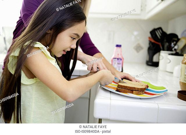 Girl in kitchen preparing sandwich
