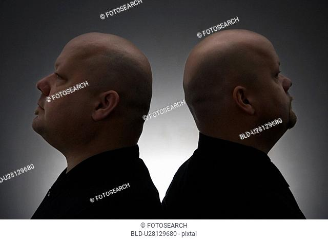 Mid adult bald identical twin men standing back to back