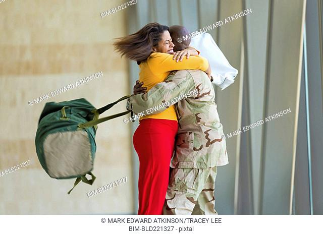 African American soldier hugging wife in airport