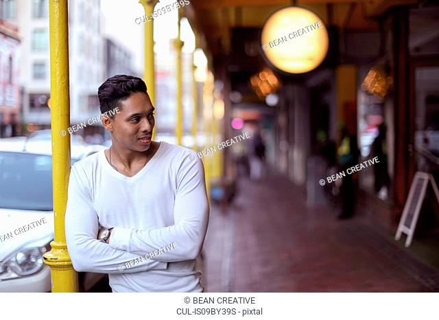 Young man standing outside shopping arcade, Cape Town, Western Cape, South Africa