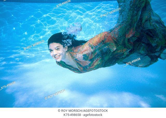 Woman in dress swimming underwater
