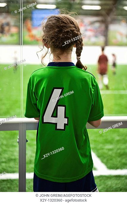 Young female athlete watches a soccer game in progress