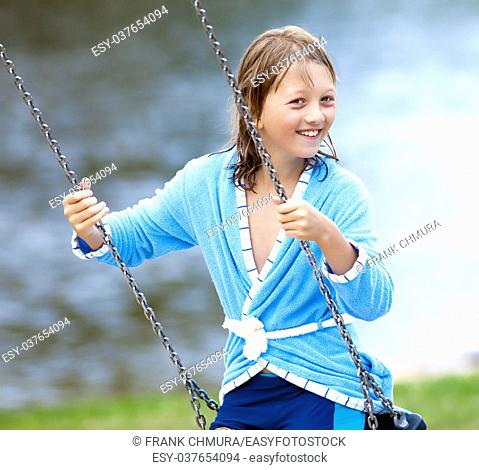 Portrait of a Boy with Blond Long Hair on a Swing