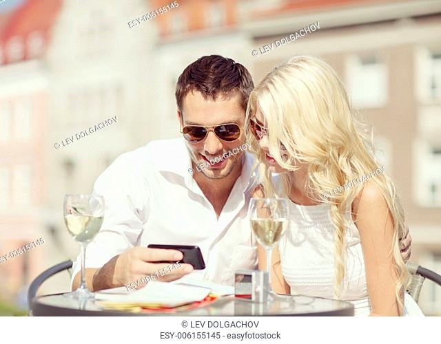summer holidays, dating and technology concept - couple looking at smartphone in cafe in the city