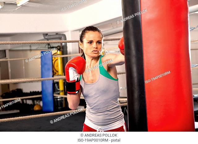 Young woman hitting punching bag