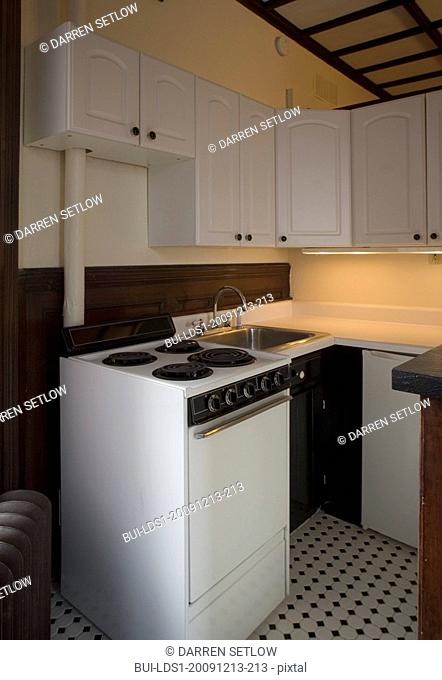 Small apartment kitchen with black and white tiled floor